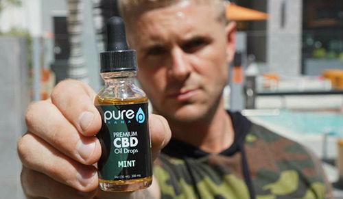 man holding cbd tincture bottle
